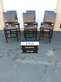two black wooden framed black leather padded armchairs 703 mi