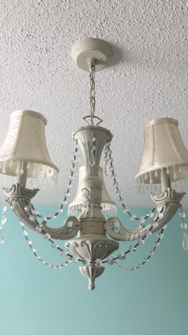 Chandelier; colour is off white/ cream. Has 3 shades and crystals.