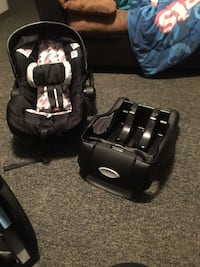 baby's black and white car seat carrier with black bracket