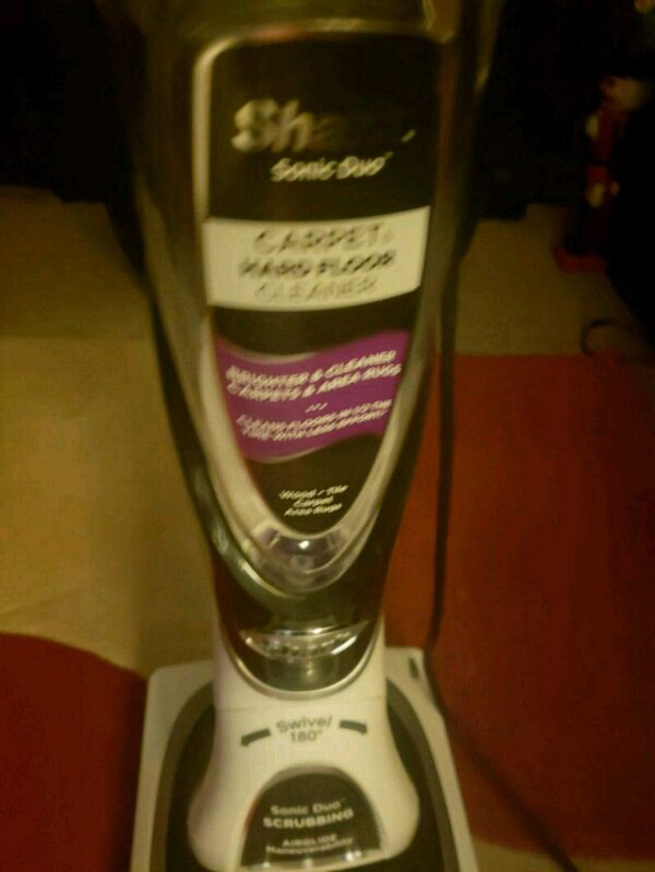 white and black upright vacuum cleaner