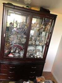 Brown wooden framed glass display cabinet two piece China with light fixtures on ceiling and two glass sliding doors Alexandria, 22304
