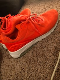 Pair of orange nike running shoes 1182 mi