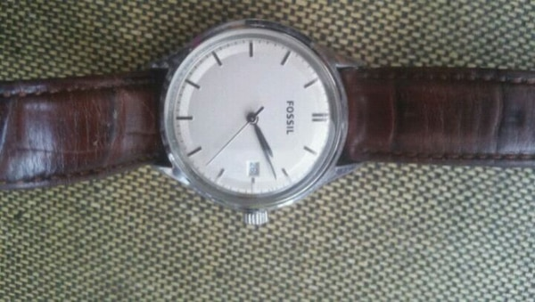 round silver analog watch with black leather strap