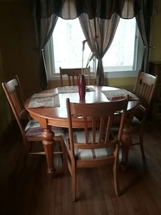 four brown wooden chairs; brown wooden round top table