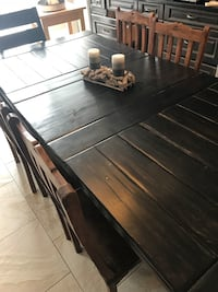 Solid hardwood rustic table and chairs.  Seats 8 middle leaf comes out.  Will deliver once viewed and paid