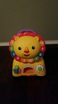 toddler's yellow Fisher-Price Musical Lion ride-on toy Kyle, 78640