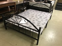 black metal bed frame with white mattress