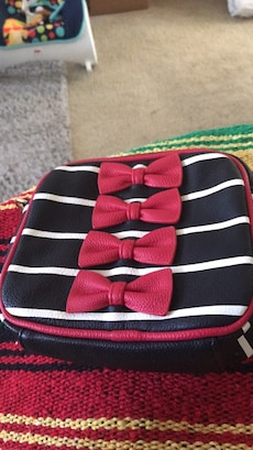 white, black, and red leather bag