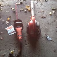 red and black electric hedge trimmer and red electric leaf blower