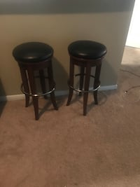 Two brown wooden stand black leather stools Houston, 77065
