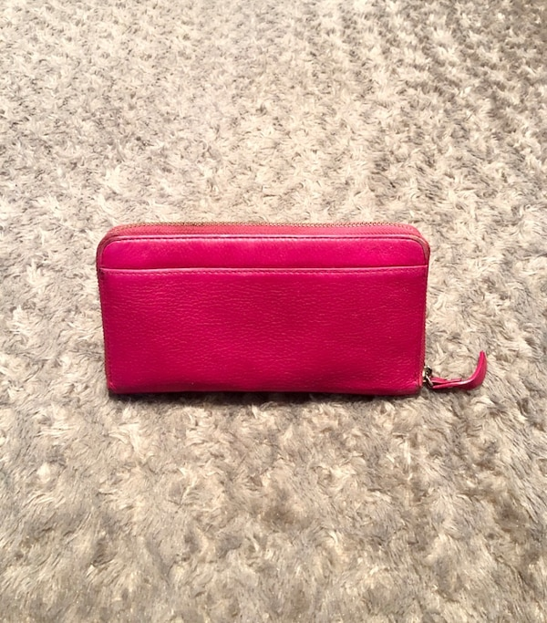 """Kate Spade wallet paid $178 good condition. The wraparound zip opens to a lined interior with a dividing zip pocket, checkbook compartment, 2 bill slots, and 12 card slots. Exterior back pocket. Measurements 7 ¾""""W x 4""""H x 1""""D. Has minor imperfections in o 9212c881-35f2-448e-9dc1-ca068a614052"""