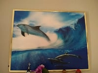 poster of school of dolphin near tidal wave with gold-colored frame