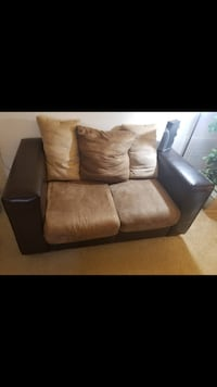 Black and brown sofa loveseat and chair with ottoman . It has signs of wear and tear