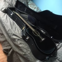 Black cutaway acoustic guitar in gig bag