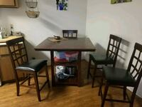 rectangular brown wooden table with four chairs di Tempe, 85282