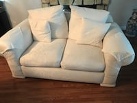 White loveseat with feathers pillows