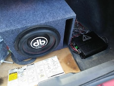 black and white car subwoofer with blue ported enclosure
