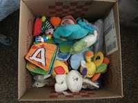 Box of baby items and a couple blankets