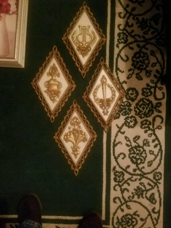 four white-and-gold wall decors