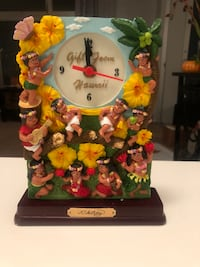 """Gift From Hawaii table clock. Quartz movement battery operated timepiece. The clock is adorned with 10 keiki boys and girls dressed for hula. The clock is 8""""h and 6""""w and 2""""d Honolulu, 96817"""