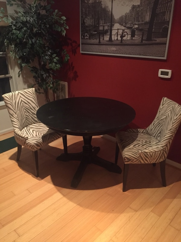 Round black wooden table with two chairs