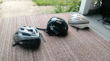 three assorted bicycle helmets