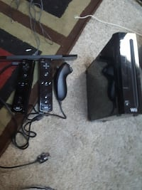 black Nintendo Wii console with three black controllers