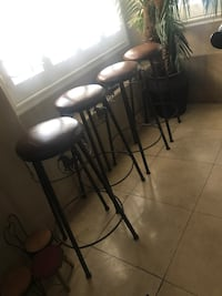 Four round black steel brown leather padded high stools