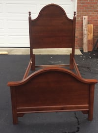 "Twin size cherry bed frame by Bassett includes headboard, footboard and side rails; headboard 60 x 42"" like new."
