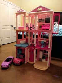 Barbie Dream House doll house with cars and furniture.