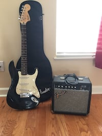 black and white stratocaster electric guitar with amplifier Chantilly, 20151
