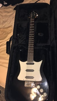 black and white stratocaster electric guitar in case