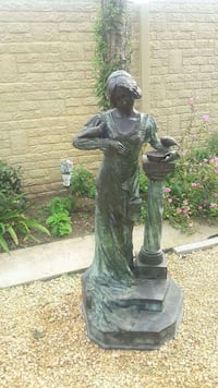 woman wearing scoop neck dress feeding bird garden statue Paris
