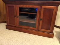 brown wooden TV stand with cabinet