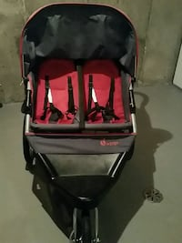 baby's black and red inStep twin jogging stroller