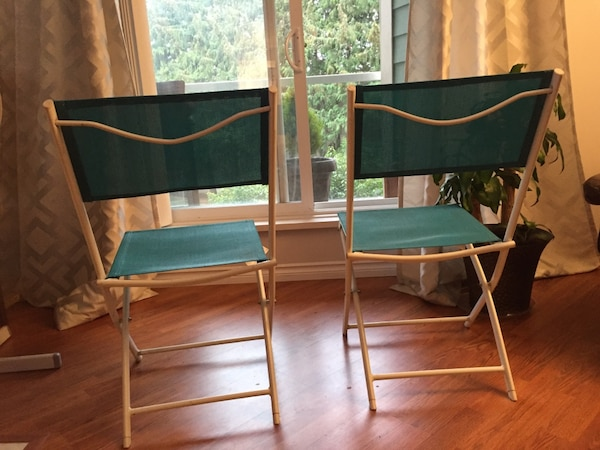 Two green outdoor chairs 701d6e44-b233-4f67-8796-767843dc200a