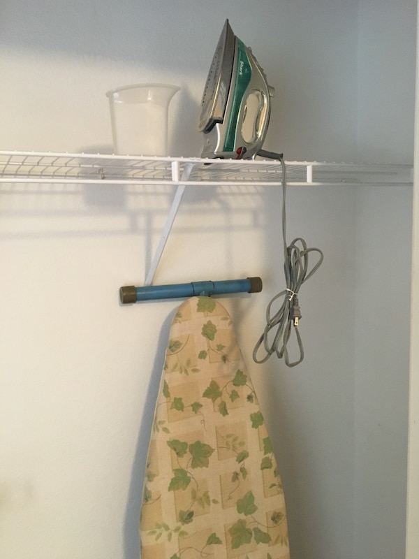 White and green floral ironing board and Shark iron