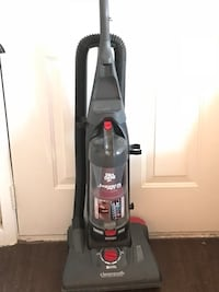 gray and red Bissell upright vacuum cleaner