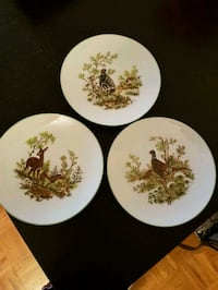 four white-and-green floral ceramic plates