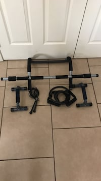 Black and gray pull up  bar, pushup  bars, jump rope, and resistance band