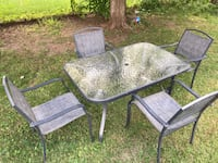two gray metal framed glass top patio table set