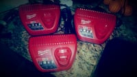 three red Milwaukee battery chargers