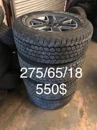 gray and black 6-spokes vehicle wheel with 275/65/18 Goodyear Wrangler tires