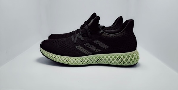 unpaired black and green adidas low-top sneaker