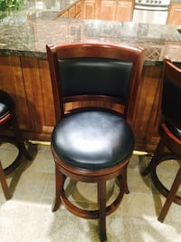 Three brown wooden framed black leather barstools