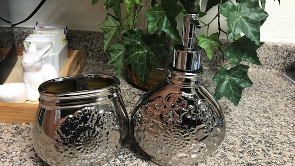 Two gray stainless steel floral pump bottle and jar