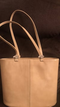 Beige purse with bumble bee accents on front straps . Peekskill, 10566