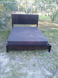 brown wooden bed with mattress