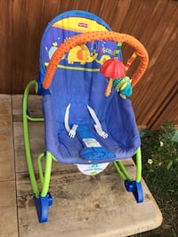 blue and green Fisher-Price bouncer