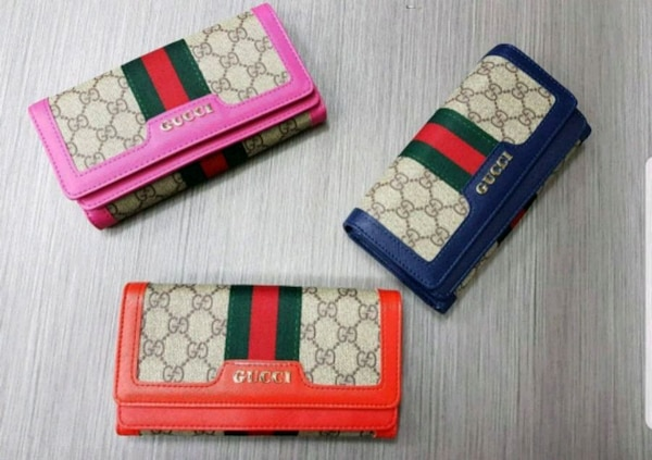 three assorted-color monogrammed Gucci bifold wallets